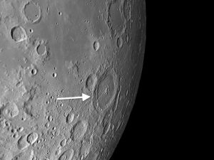 The principal rille, Rima Petavius, is a graben, an elongated depression that results when stresses open up two parallel cracks in the lunar crust and the terrain in between drops.